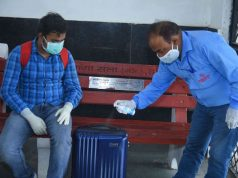 Disinfecting passenger luggage on platforms with Godrej Protekt On the Go Disinfectant Spray